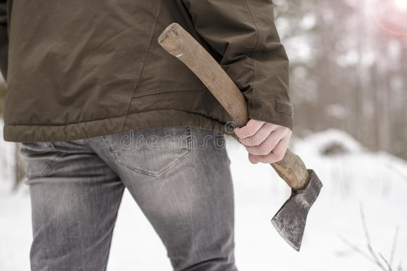有一个轴的人在他的手上在冬天积雪的森林,冷淡的天里进来 库存照片