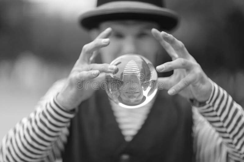 有一个透明不可思议的球的一个小丑人在他的手上 免版税库存照片