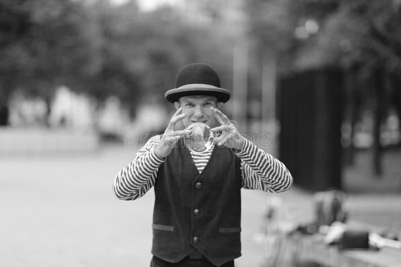 有一个透明不可思议的球的一个小丑人在他的手上 免版税库存图片
