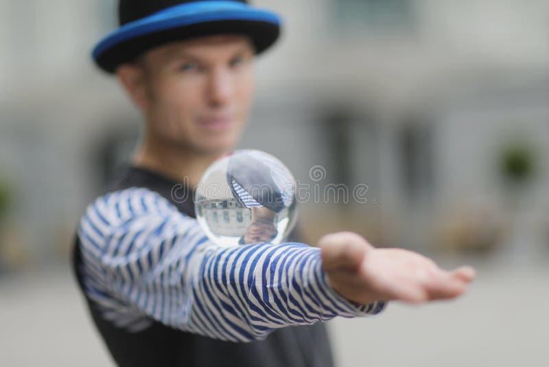 有一个透明不可思议的球的一个小丑人在他的手上 库存照片