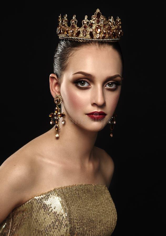 有一个金黄冠、耳环和profes的美丽的深色的女孩 免版税图库摄影