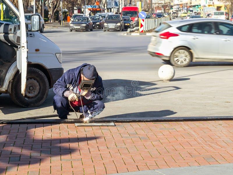有一个防毒面具和手套的一位焊工蹲并且执行焊接的工作或迫切修理在城市街道上 免版税图库摄影