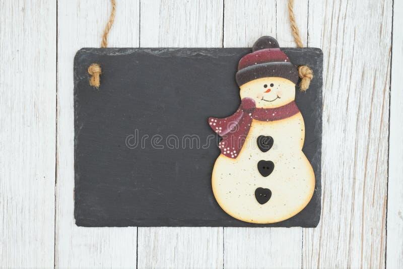 有一个雪人的空白的垂悬的黑板在被风化的白涂料织地不很细木头背景 免版税库存图片