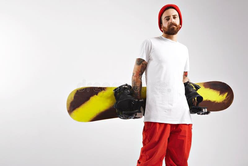 有一个雪板的年轻人在演播室 库存图片