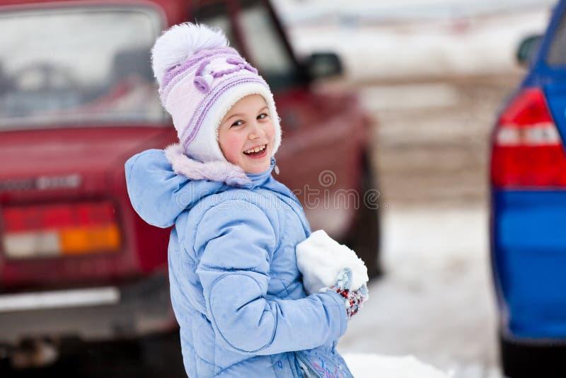 有一个雪球的女孩在手上 免版税库存照片