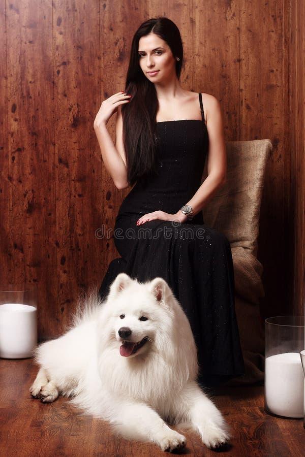 有一个雪白狗萨莫耶特人多壳的演播室的美丽的深色的长期少妇黑色礼服在棕色蜡烛树荫下  免版税图库摄影