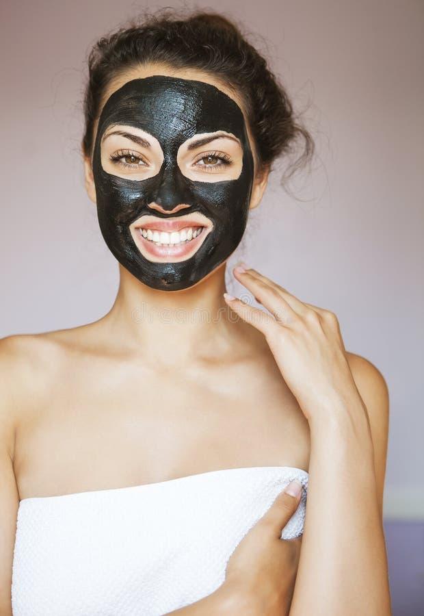 有一个面具的少妇治疗黑色mu的面孔的 免版税库存照片