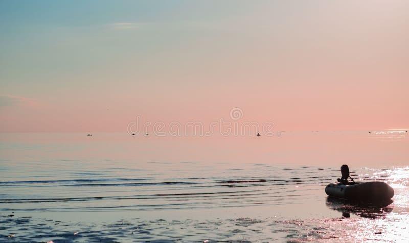 有一个马达的橡皮艇在反对桃红色日落的海 免版税库存图片