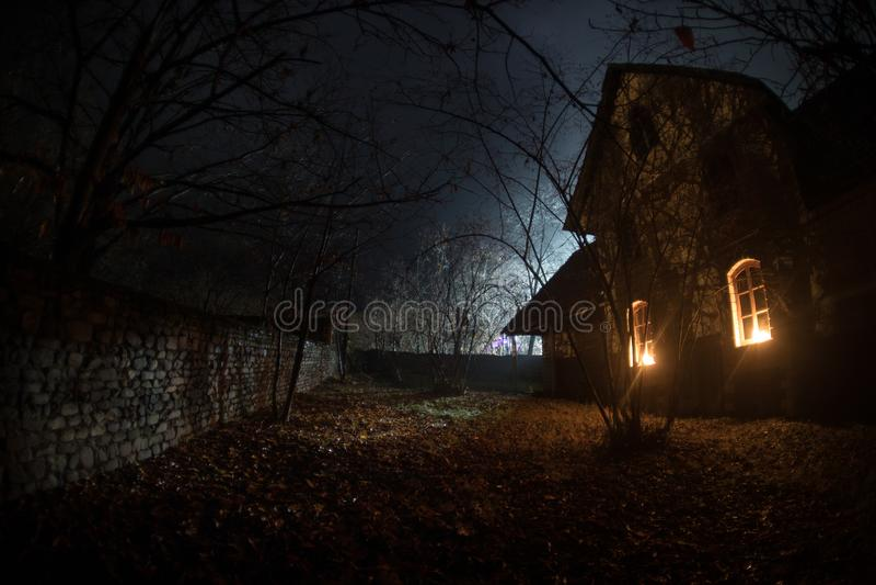 有一个鬼魂的老房子在森林里在晚上或雾的被放弃的被困扰的恐怖议院 老神秘的大厦在死的树森林里 免版税图库摄影