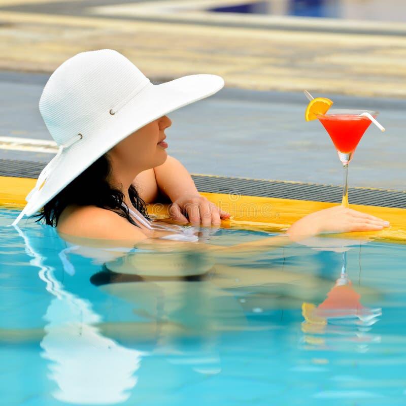 有一个鸡尾酒的女孩在游泳池的边缘 库存照片