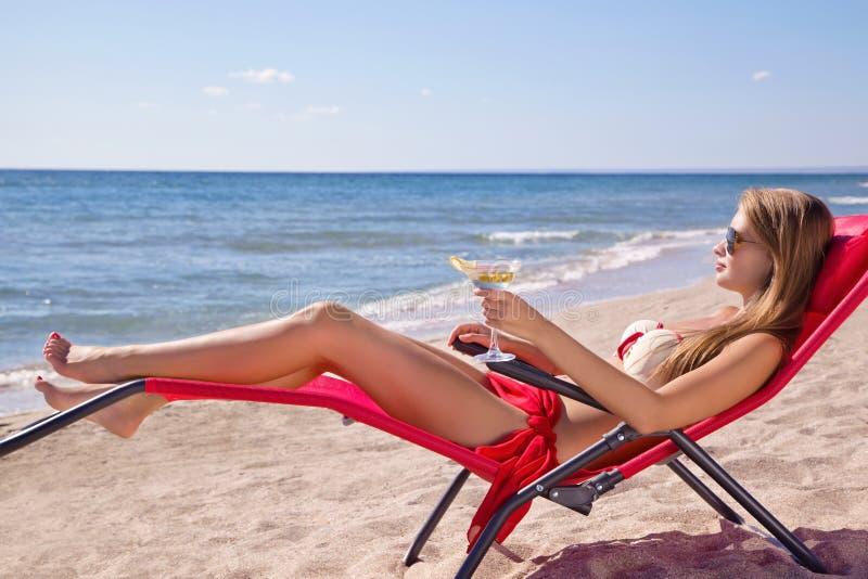 有一个鸡尾酒的马蒂尼鸡尾酒女孩在海滩 图库摄影