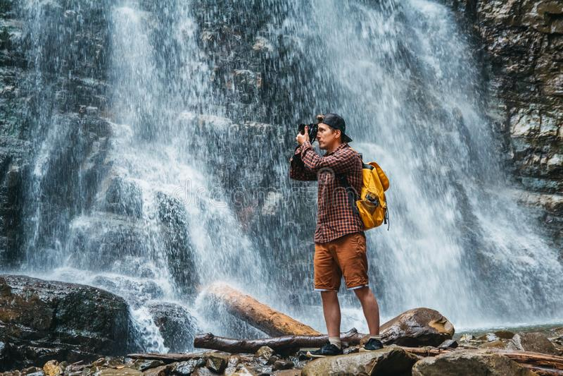 有一个黄色背包身分的旅客人在瀑布的背景做一个照片风景 r 免版税库存图片