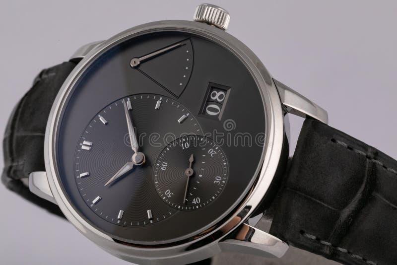 有一个黑拨号盘的精神银色手表,有在白色背景隔绝的黑皮带的黑顺时针测时器秒表 图库摄影