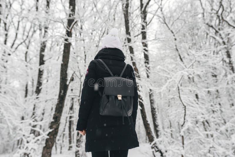 有一个黑背包的女孩在一个多雪的森林里 免版税库存图片