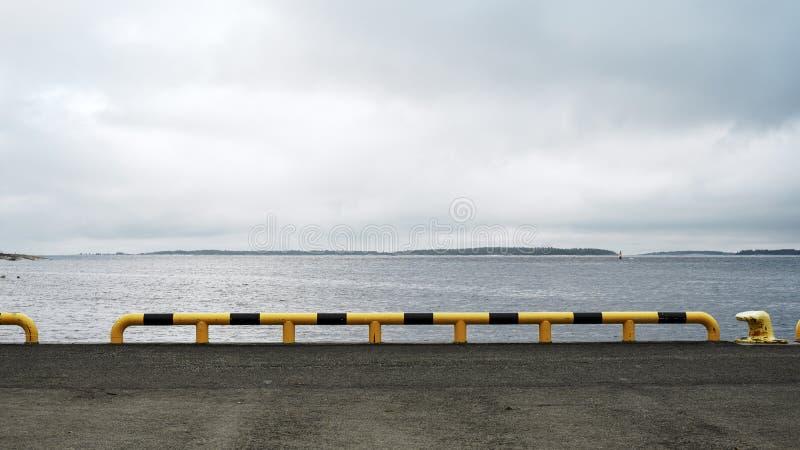 有一个黑黄色管子的码头反对天空 瑞典地点 E 图库摄影