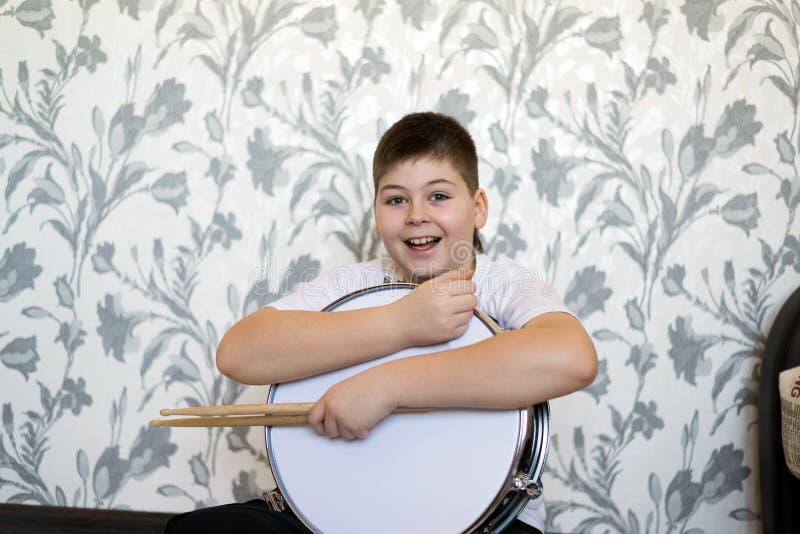 有一个鼓的少年男孩在屋子里 库存图片