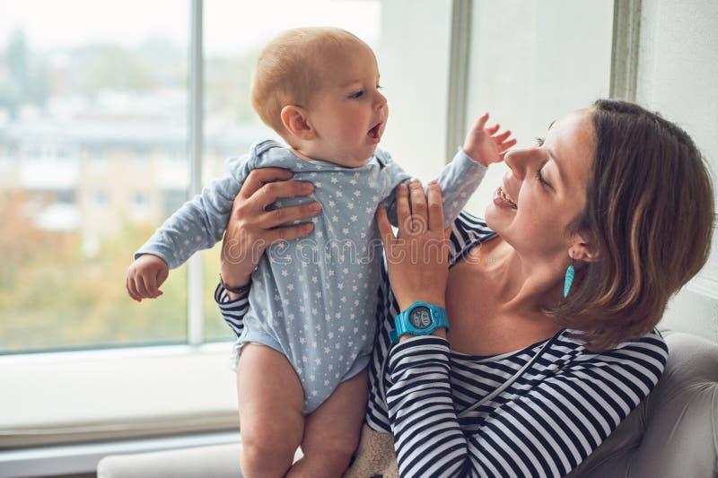 有一个8个月大婴孩的母亲在家坐沙发 免版税图库摄影