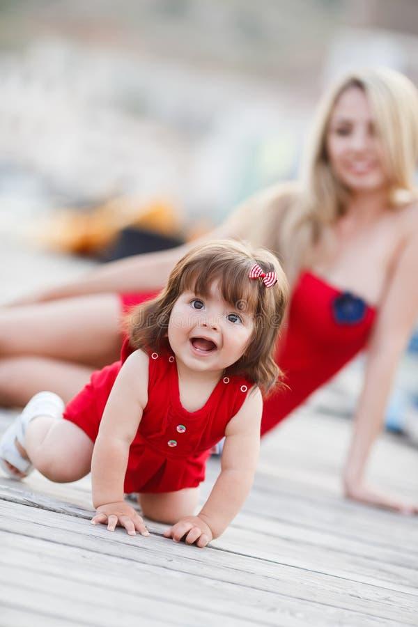 有一个年轻女儿的愉快的年轻母亲在游艇俱乐部附近 库存照片