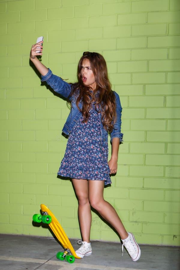 有一个黄色便士滑板的美丽的长发女孩在a附近 免版税库存图片