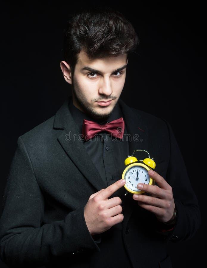 有一个黄色闹钟的英俊的人 免版税库存照片