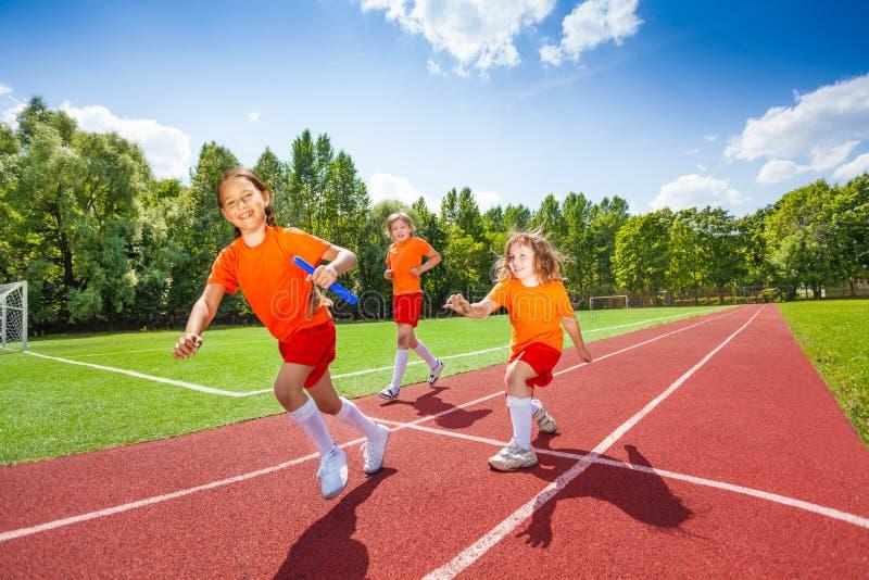 有一中转警棒赛跑的三个女孩 免版税库存图片
