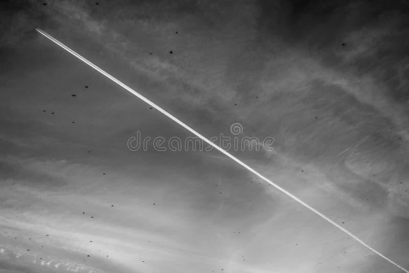 有一串足迹的飞机在天空 库存图片