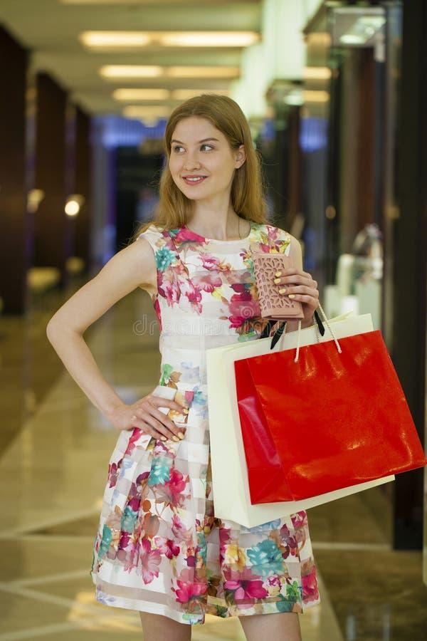 有一些购物袋的年轻白肤金发的妇女在购物中心 免版税库存照片