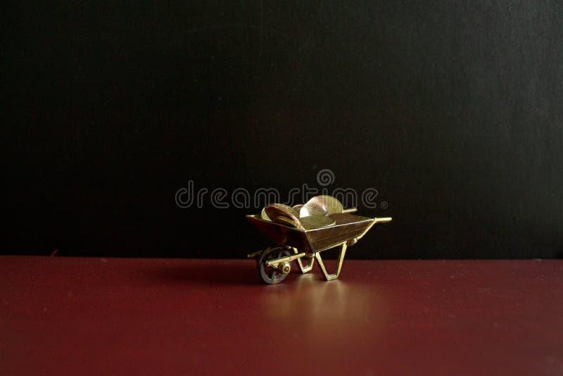 有一件小珍宝的一辆金黄独轮车在它 免版税库存照片