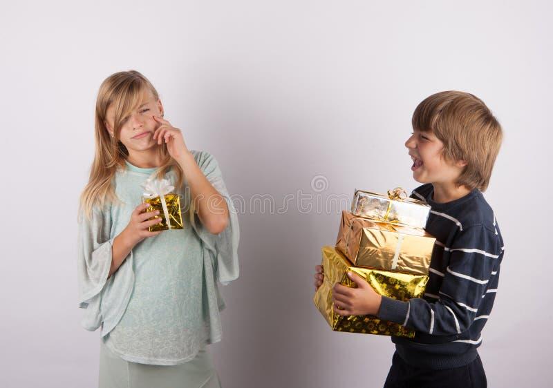 有一件小礼物和一个男孩的哀伤的女孩有laughting很多的礼物的 库存照片