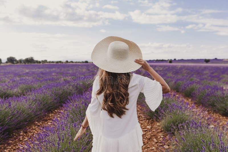 有一件帽子和白色礼服的迷人的年轻女人在日落的一个紫色淡紫色领域 生活方式户外 r 免版税库存图片