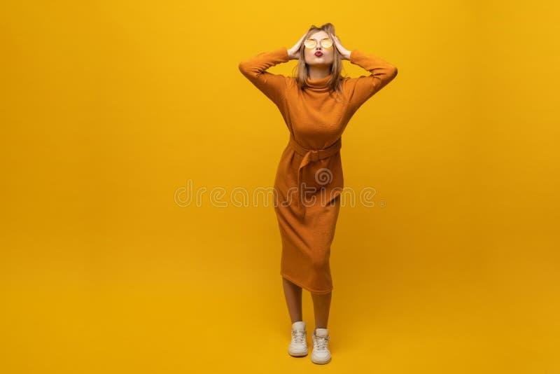 有一件快乐的美女佩带的礼服的全长画象乐趣和跳舞被隔绝在黄色背景 免版税库存图片