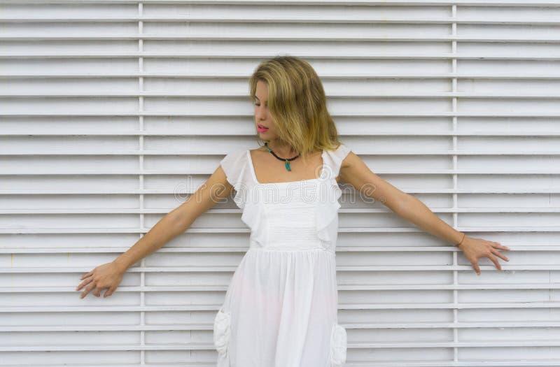 有一件白色礼服的白肤金发的女孩在白色背景中 免版税库存图片