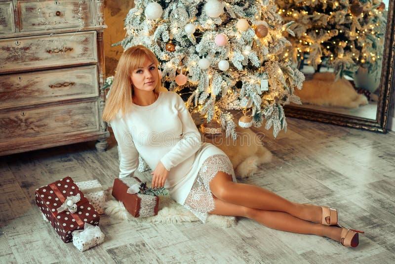 有一件礼物的美丽的年轻女人在圣诞树 库存照片
