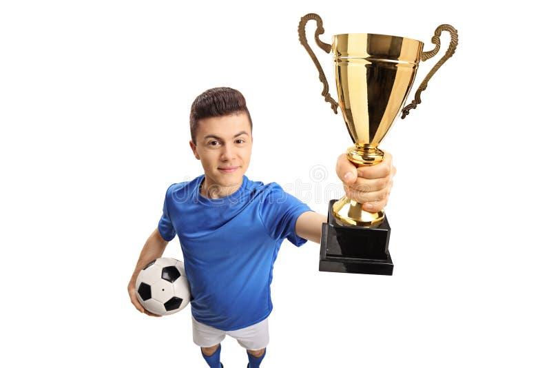 有一件金黄战利品的少年足球运动员 库存照片