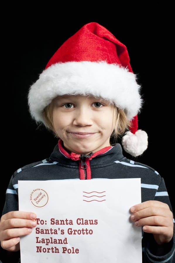 有一份信函的一个愉快的男孩圣诞老人的 免版税库存图片
