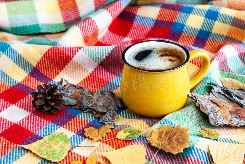 有一份热的咖啡饮料的明亮的黄色杯子在明亮的格子花呢披肩 库存图片