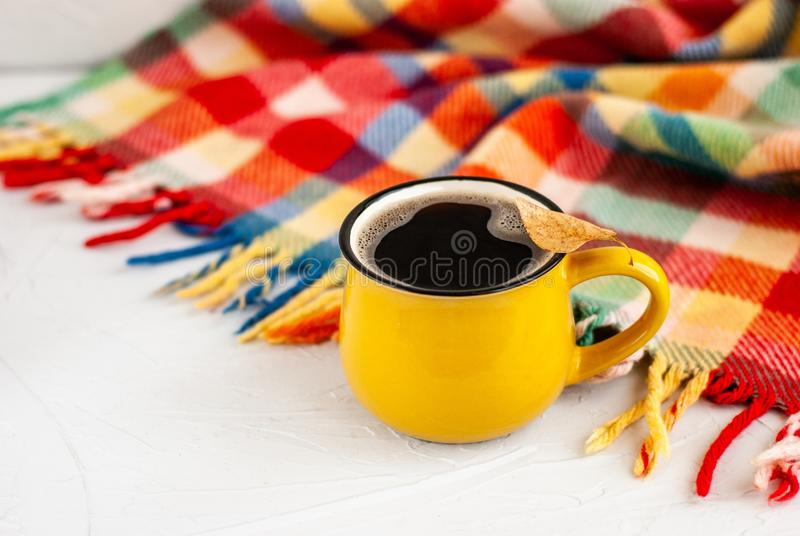 有一份热的咖啡饮料的明亮的黄色杯子,在杯子在白色背景的一片干燥秋天橙色叶子与明亮的格子花呢披肩 免版税图库摄影