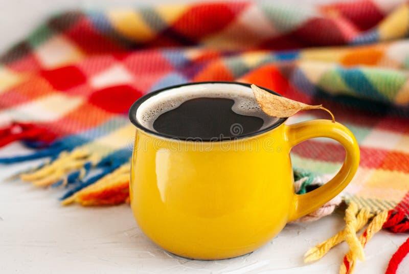 有一份热的咖啡饮料的明亮的黄色杯子,在杯子在白色背景的一片干燥秋天橙色叶子与明亮的格子花呢披肩 免版税库存照片