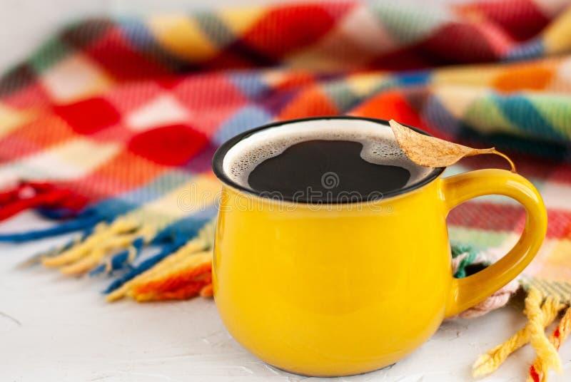 有一份热的咖啡饮料的明亮的黄色杯子,在杯子在白色背景的一片干燥秋天橙色叶子与明亮的格子花呢披肩 库存照片