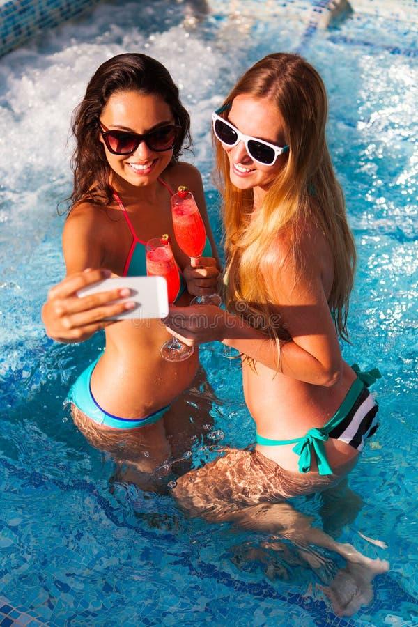 有一份饮料的愉快的女朋友在水池作为的一个夏天党 免版税图库摄影