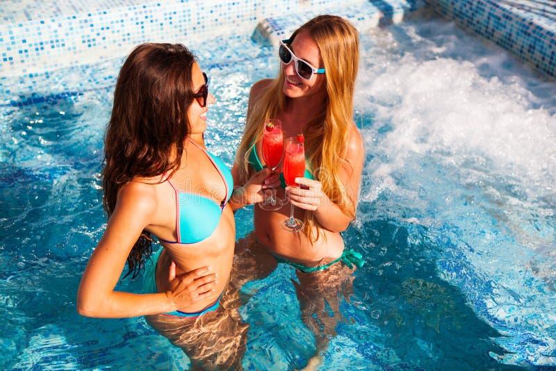 有一份饮料的愉快的女朋友在水池的一个夏天党 库存照片