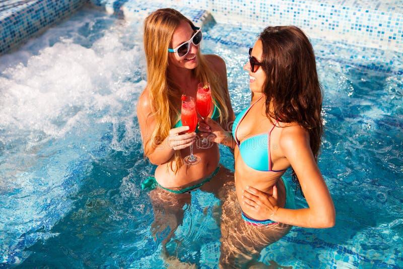 有一份饮料的愉快的女朋友在水池的一个夏天党 免版税库存照片