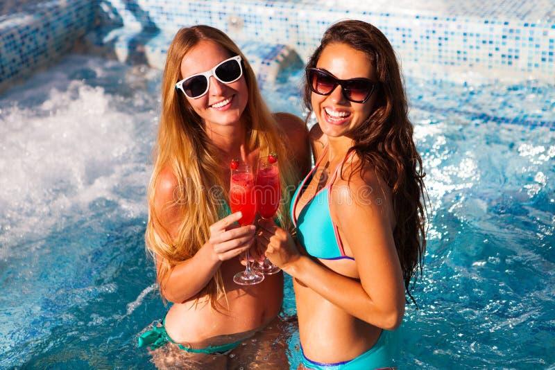 有一份饮料的愉快的女朋友在水池的一个夏天党 图库摄影
