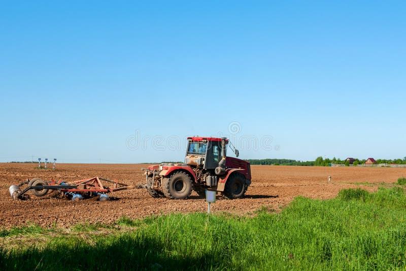 有一位红色耙圆盘耕地机的大银色拖拉机领域的在一个晴天 工作的概念在的领域和农业 库存图片