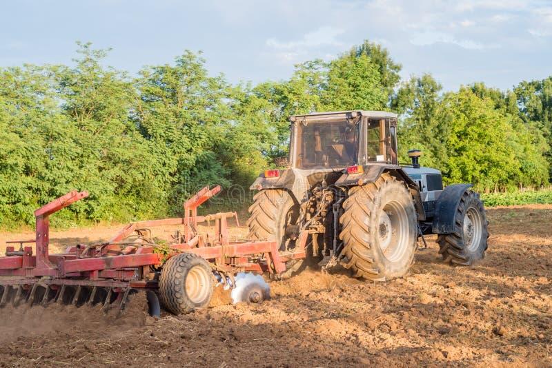 有一位红色耙圆盘耕地机的大银色拖拉机领域的在一个晴天 工作的概念在的领域和agricultur 免版税库存照片