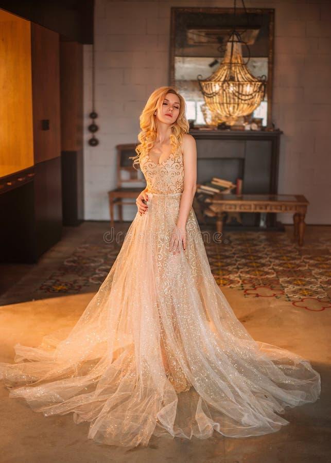有一典雅称呼的一个白肤金发的女孩在她的头发,穿戴在有长的一件豪华,豪华,金黄,闪耀的礼服 库存照片