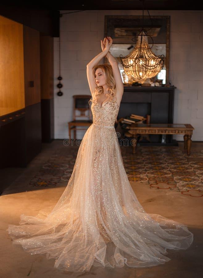 有一典雅称呼的一个白肤金发的女孩在她的头发,穿戴在有长的一件豪华,豪华,金黄,闪耀的礼服 免版税图库摄影