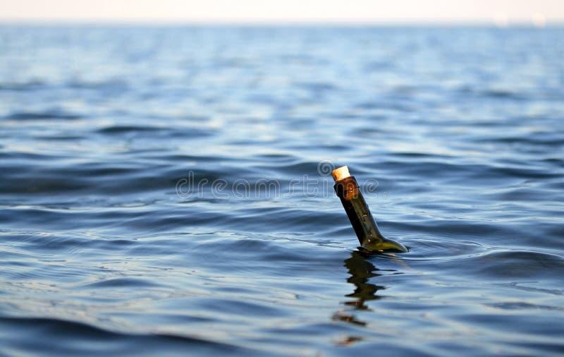 有一则秘密消息的瓶在海洋中间 库存图片