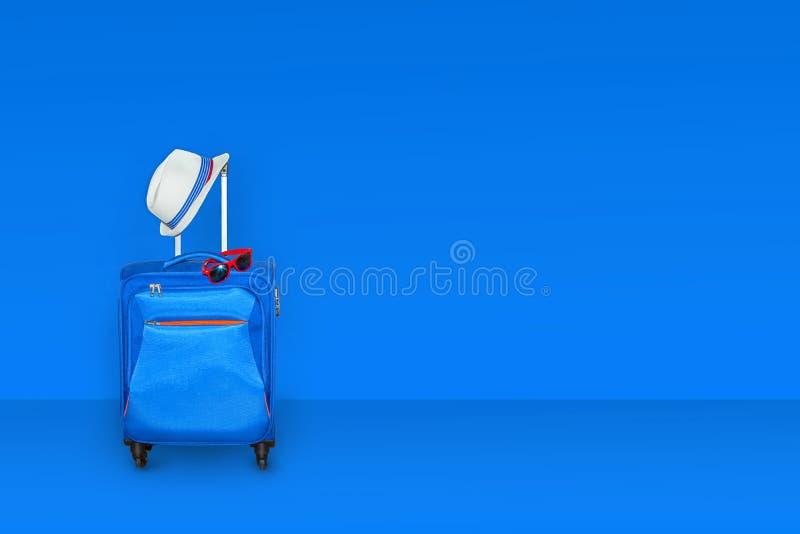 有一副夏天帽子和时兴的太阳镜的蓝色手提箱在浅兰的背景,暑假旅行概念,自由空间 图库摄影