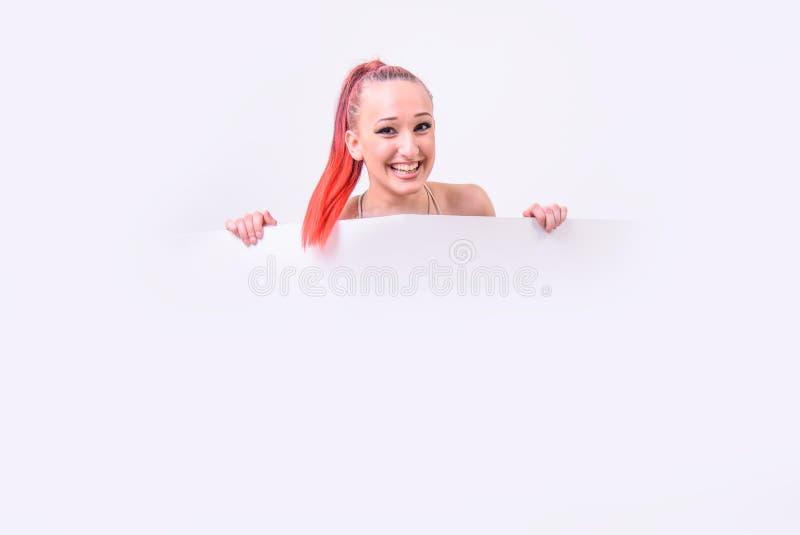 有一副白色横幅的逗人喜爱的红发妇女 库存照片